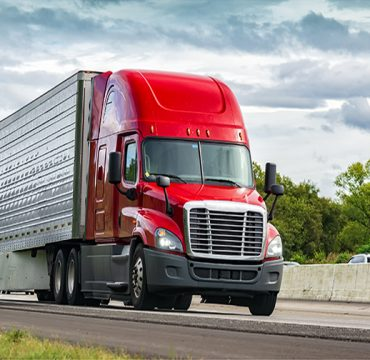 Horizontal shot of a red semi-truck on an interstate highway.